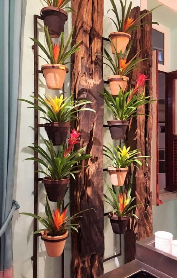 Jardim vertical com madeira e bromélias.