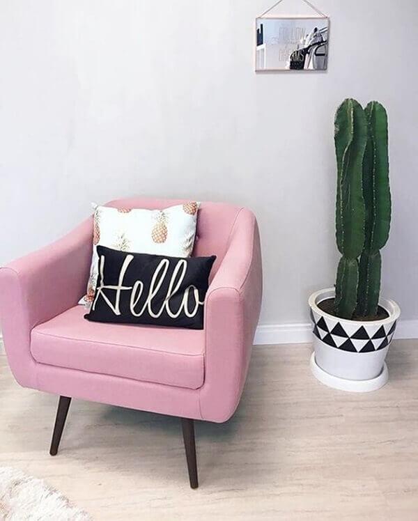 Sala feminina com poltrona rosa.