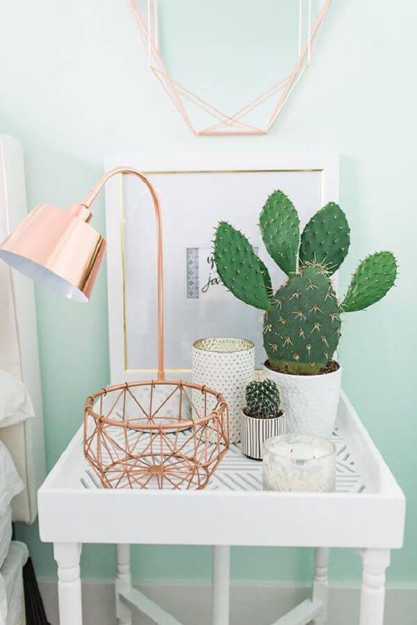 Mesa lateral branca com objetos em rose gold.