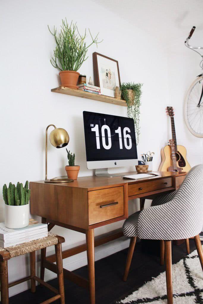 Escritório com escrivaninha de madeira e decoração clean.