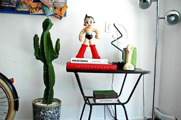 Decoração com livros, plantas e esculturas.