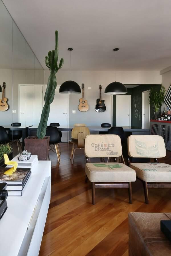 Sala moderna com violão, mesa e cacto.