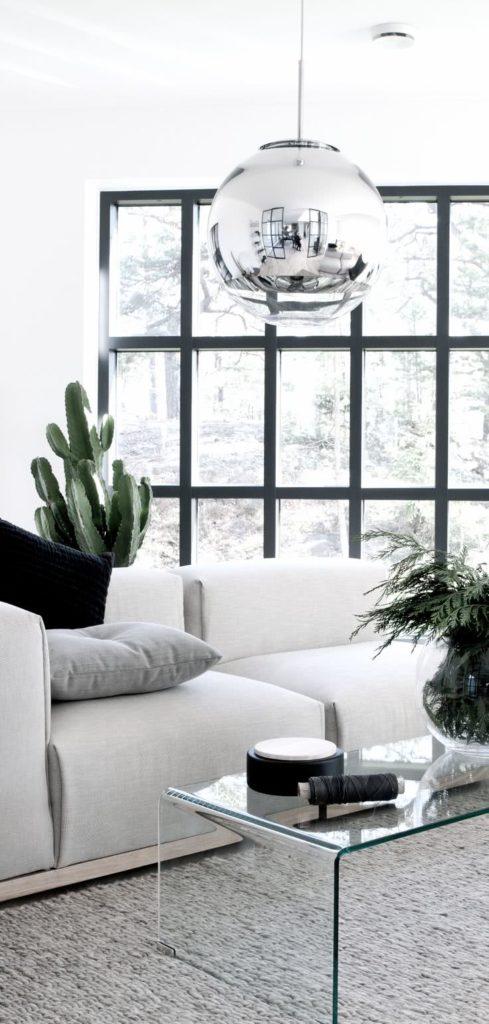 Sala moderna preta e branca com mesa de centro de vidro.