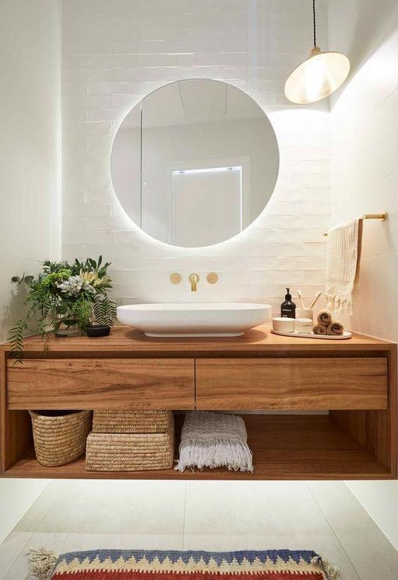 Banheiro branco com espelho redondo.