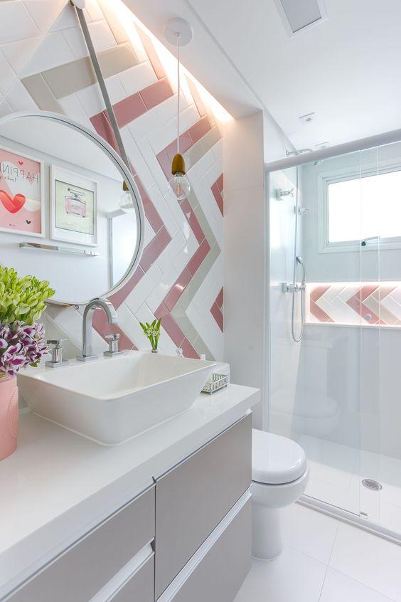 Banheiro feminino com azulejos branco e rosa.