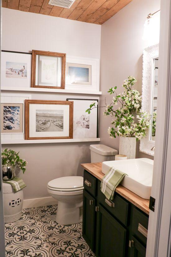 Lavabo decorado com quadros e plantas.