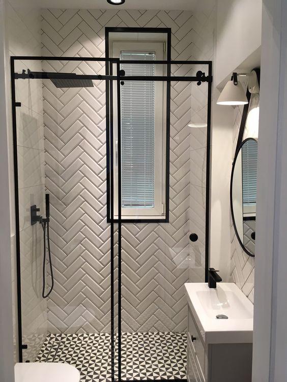 Banheiro preto e branco com azulejos na diagonal.
