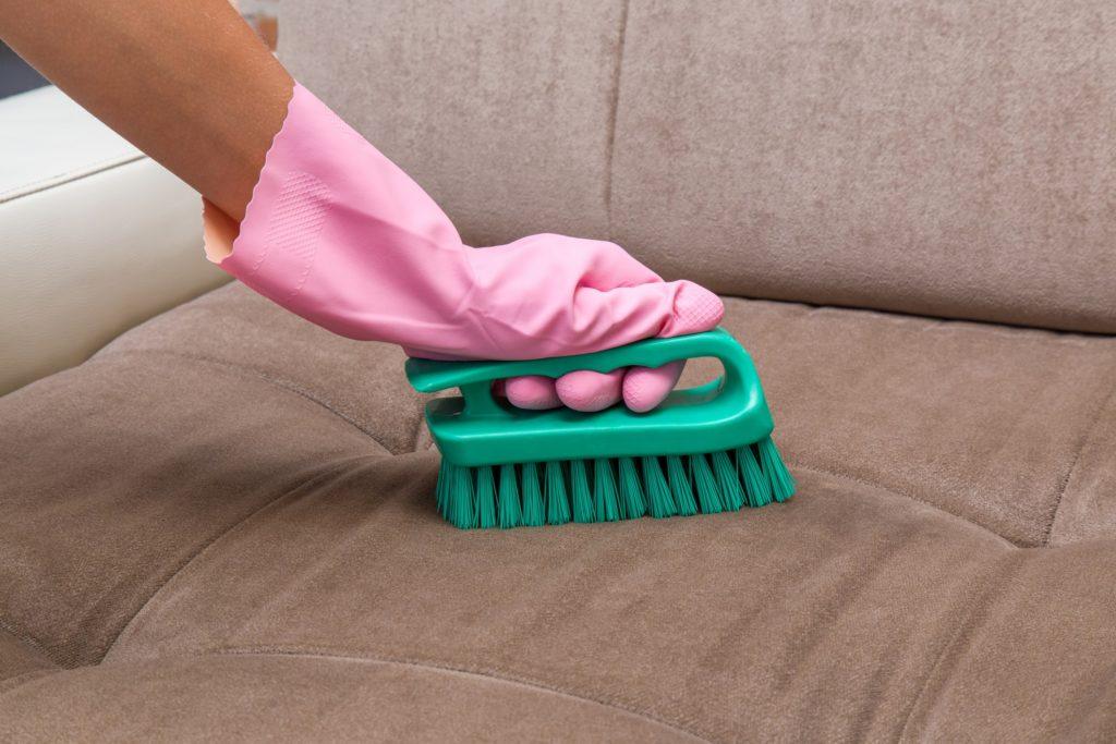Limpeza de sofá com luvas e escova.