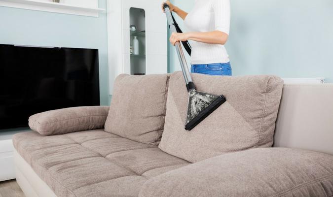 Limpeza de sofá a seco com aspirador de pó.