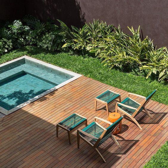 piscina de quintal com lateral de madeira e cadeiras