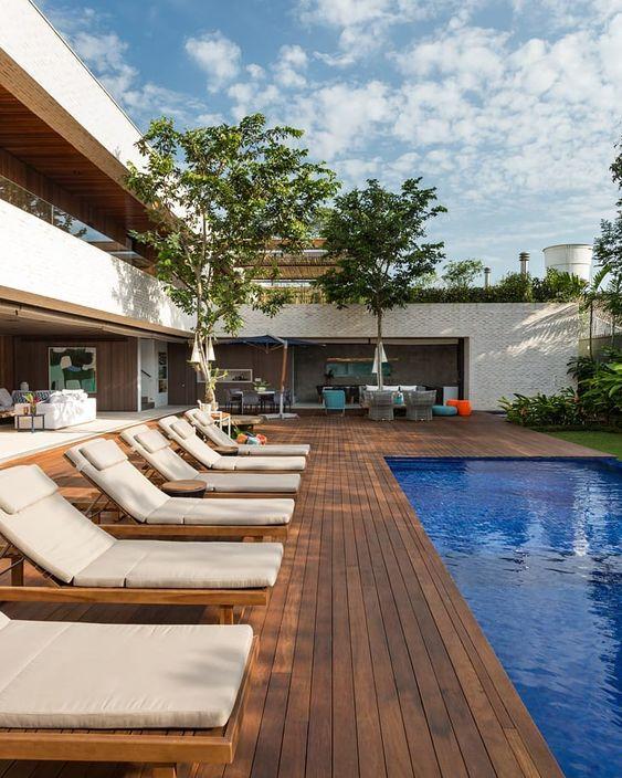 área externa com deck de madeira grande na piscina