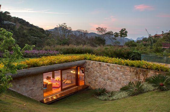 casa na natureza com teto verde e paredes de pedras com jardim