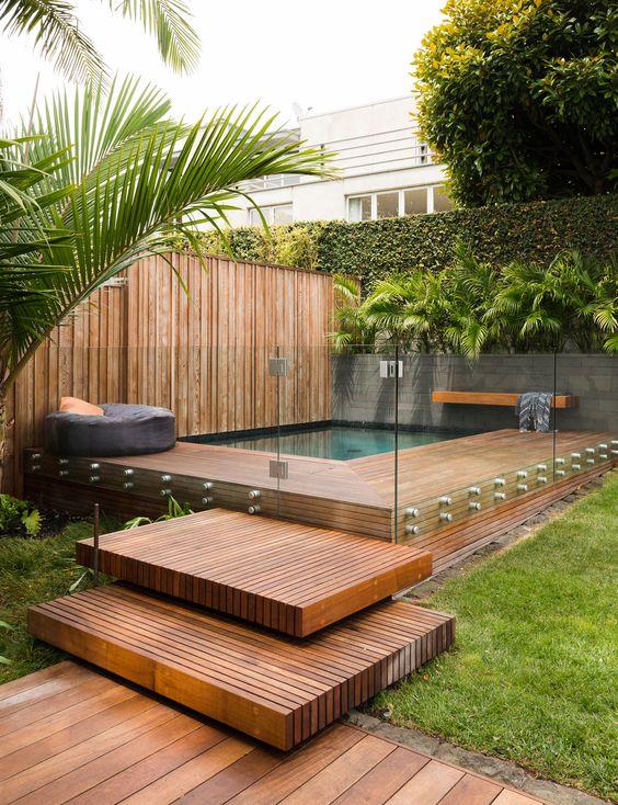 piscina com deck de madeira e paredes de vidro