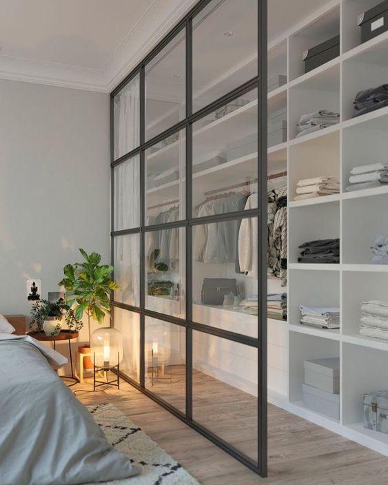 closet com divisória de vidro ao lado da cama