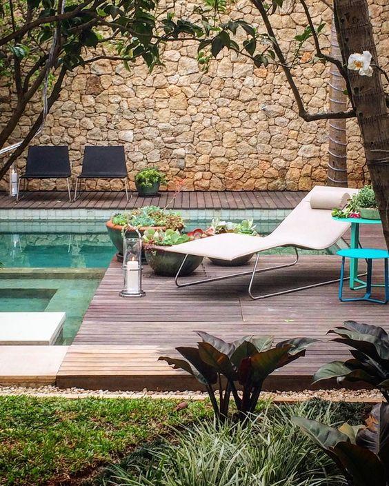 piscina com deck de madeira e parede de pedra