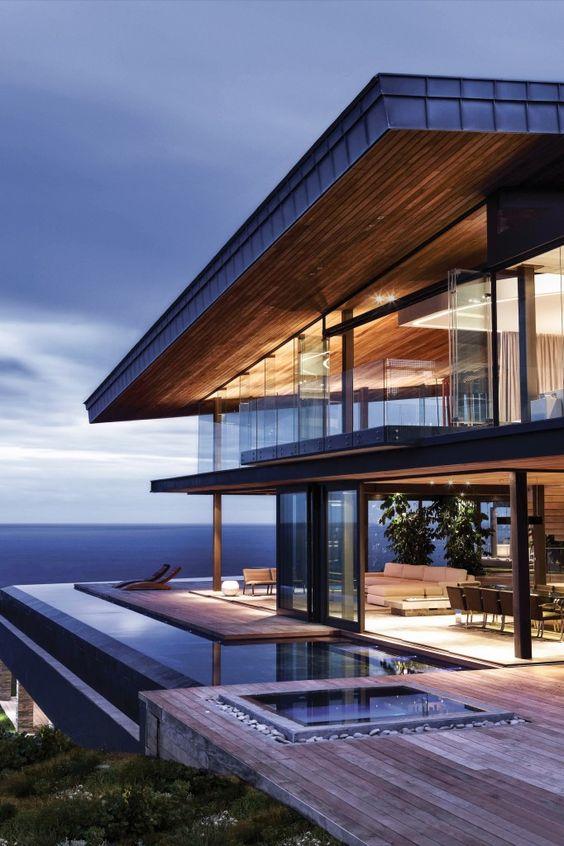 casa grande com piso de madeira e piscina em torno