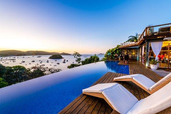 piscina borda infinita com vista infinita para o mar e cadeiras para descanso