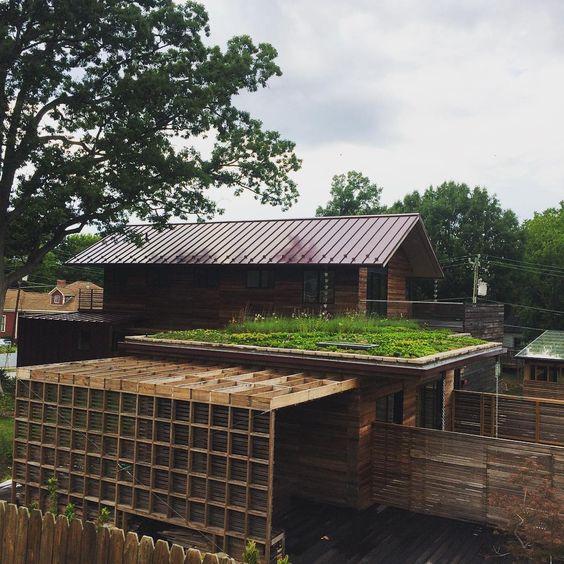 ecotelhado em casa de madeira envolta de árvores