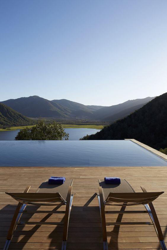 piscina com piso em madeira e vista para as montanhas