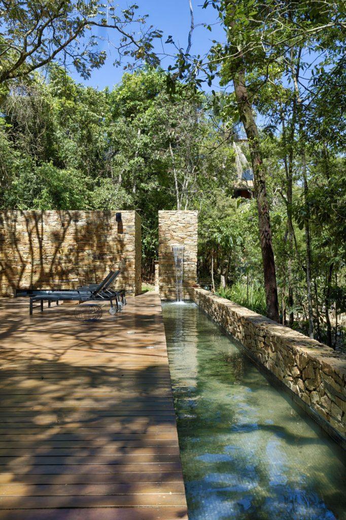 piscina com deck de madeira e pedras