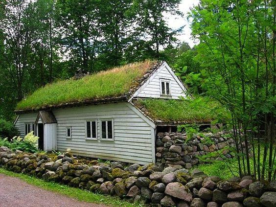 casa branca de madeira rústica com teto verde e pedras na lateral