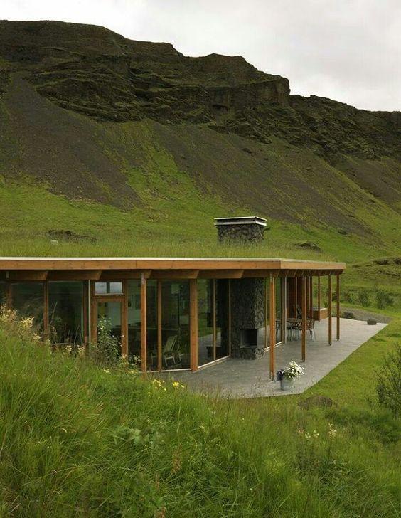 casa integrada com paredes de vidro em montanha em teto de vegetação