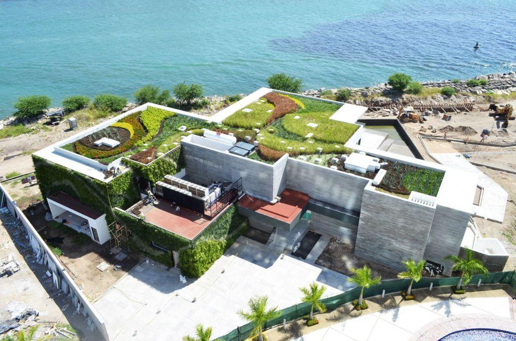 casa grande com teto verde beirando o mar