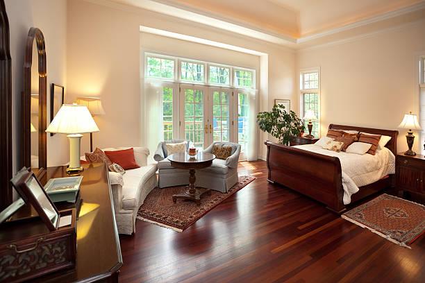 quarto com grande vidraça, paredes claras e móveis em madeira