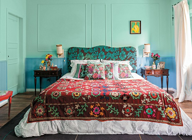 quarto com paredes em tons azul e verde com roupa de cama florida