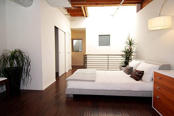 espaço para dormir com luminária acima da cabeceira e móvel lateral