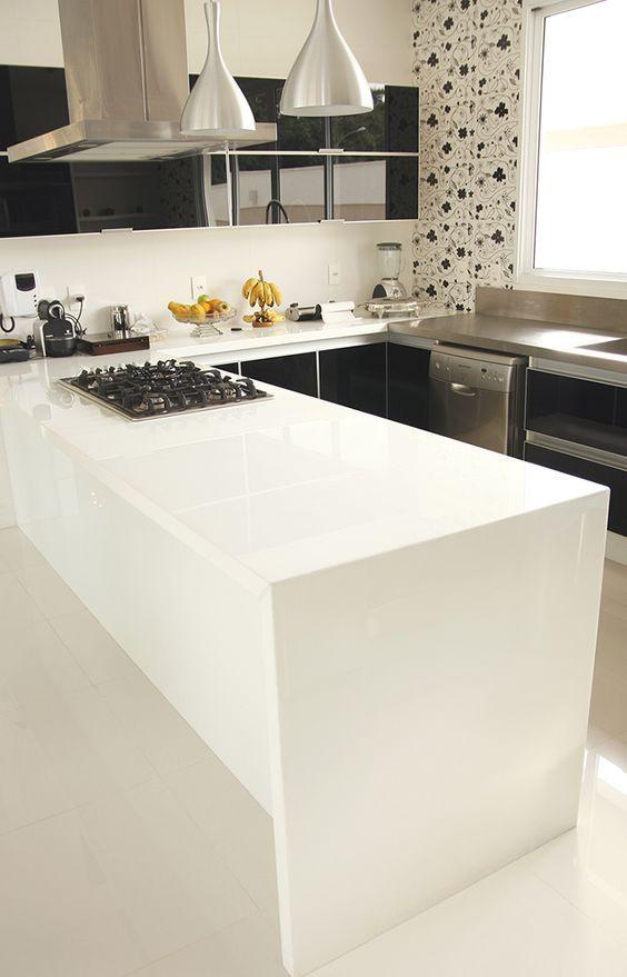 Balcão branco com fogão preto.