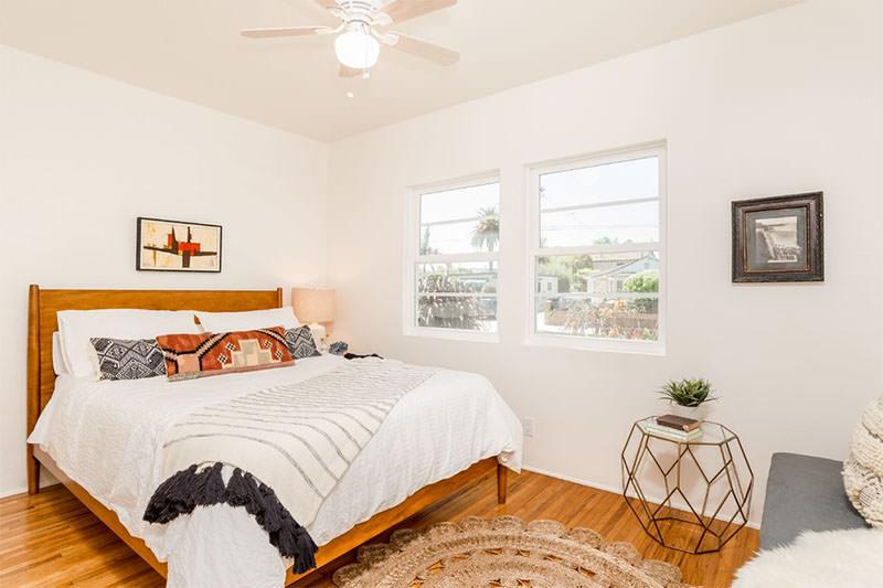 cama cabeceira de madeira lisa e almofadas estampas geométricas