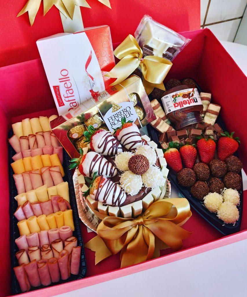 caixa com chocolate, frutas e frios