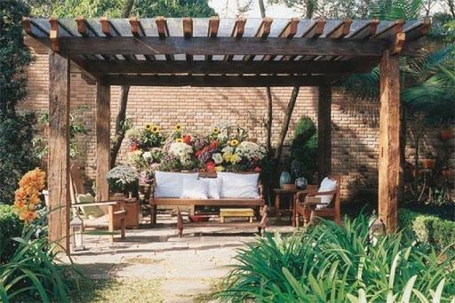 pergolado de madeira com flores e sofás